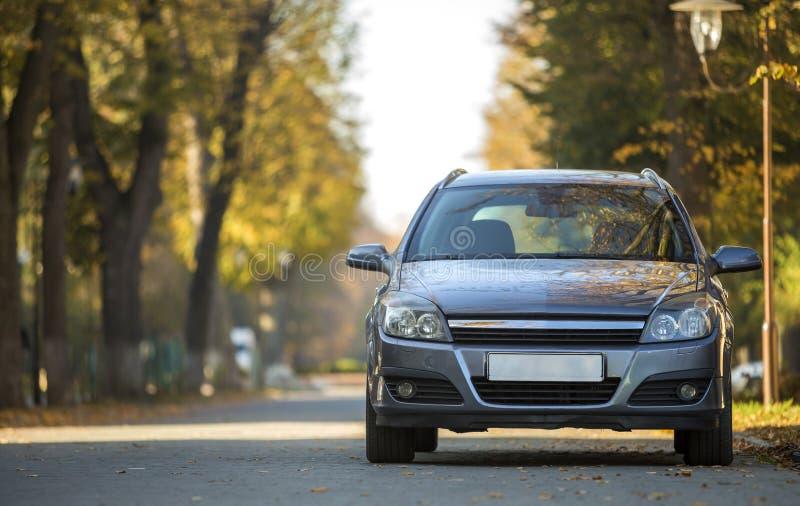 Вид спереди серого сияющего пустого автомобиля припаркованного в тихом районе на дороге асфальта на фонарном столбе на запачканно стоковая фотография rf