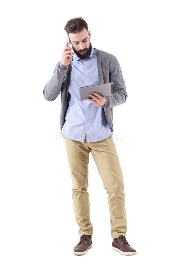 Вид спереди серьезного бородатого работодателя на телефоне смотря планшет стоковые изображения