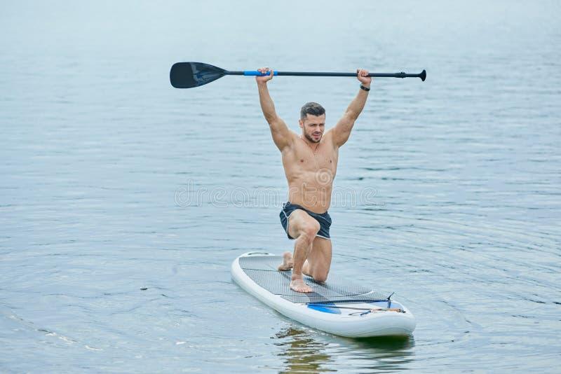 Вид спереди спортсмена держа длинное весло, плавая на доске маленького глотка в озере города стоковое фото