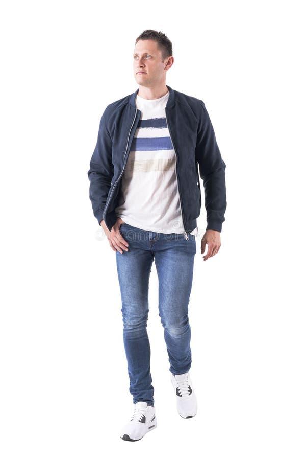 Вид спереди уверенно вскользь мужеского человека в джинсах и куртке идя и смотря вверх стоковое фото