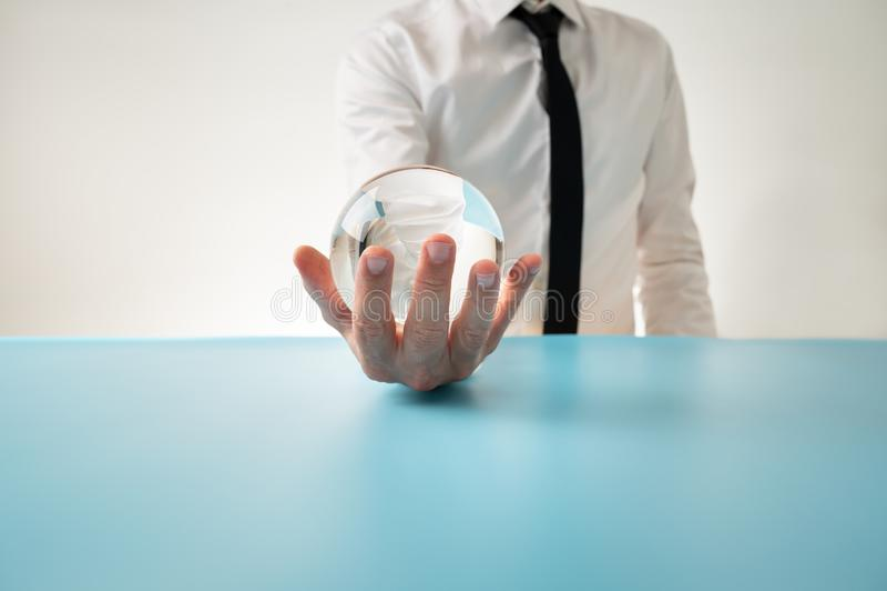 Вид спереди человека в элегантной рубашке и связи держа кристаллическую сферу в его руке стоковая фотография