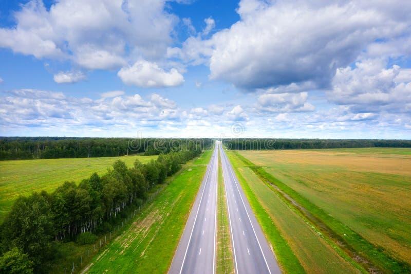 Вид с воздуха дороги на солнечный летний день Пустое шоссе сверху Красивый ландшафт дороги между зеленым лугом и голубым небом стоковая фотография rf