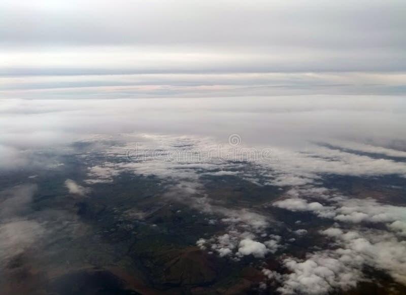 Вид с воздуха земли при белые облака покрывая небо и зеленую землю с горами и море видимое ниже стоковые изображения