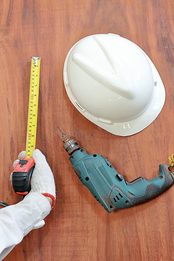 Вид с воздуха инструментов древесины работая на деревянной предпосылке Измеряя лента, шлем безопасности, электрический сверлильны стоковое фото rf