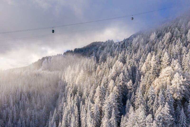 Вид с воздуха над снежной долиной с облаками, подниматься гребня горы фуникулера Transportatio гондолы леса зимы горы туристское стоковая фотография