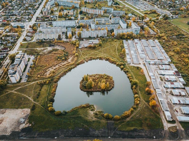 Вид с воздуха на небольшой пруд с островом, окруженный советскими многоквартирными домами в городе Елгава Латвия стоковая фотография rf