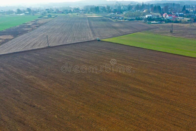 Вид с воздуха на польском сельском районе со старым трактором пока вспахивающ почву на пшеничном поле перед засевать семена стоковая фотография
