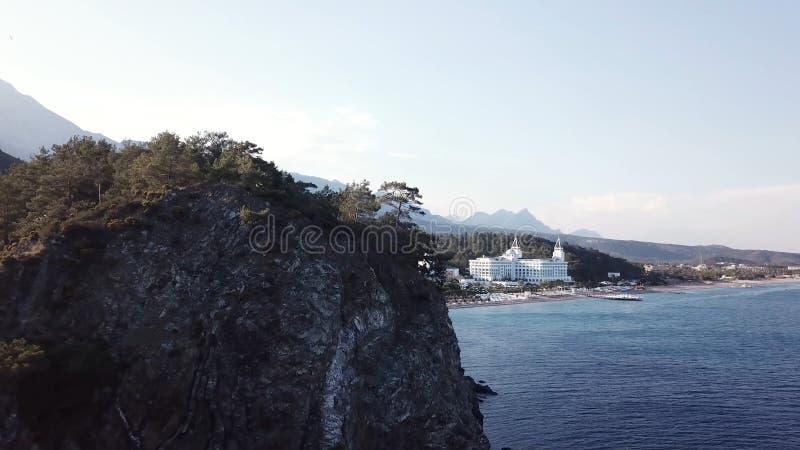 Вид с воздуха на seashore с роскошной гостиницей с предпосылкой леса и гор и голубым небом видео Красивая верхняя часть лета стоковые фотографии rf