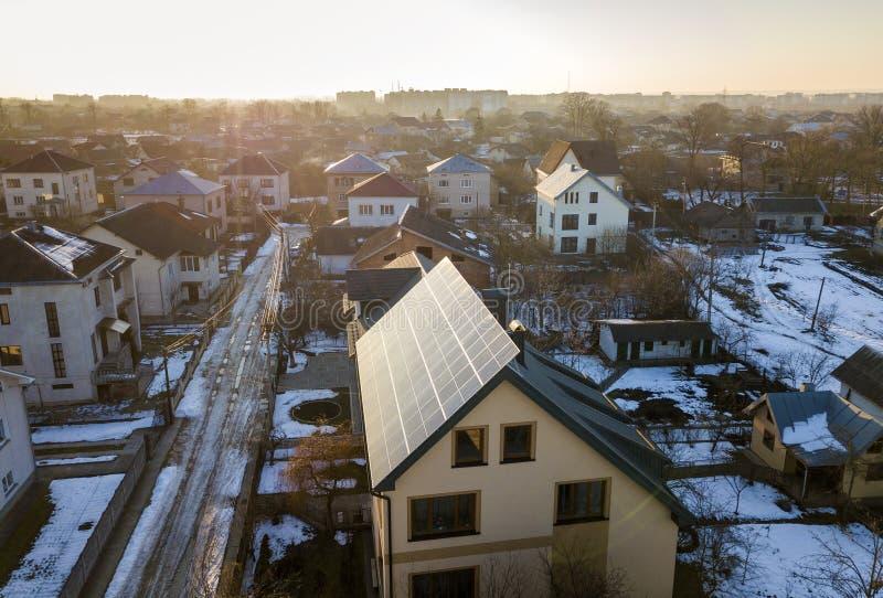 Вид с воздуха нового современного коттеджа дома 2 рассказов с системой панелей голубого сияющего солнечного фото voltaic на крыше стоковое фото