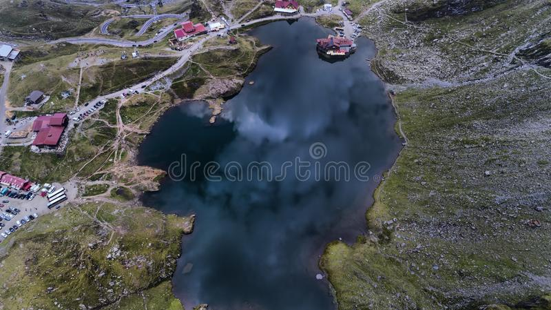 Вид с воздуха о небольшом озере на бурный день, на верхней части гор Fogaras, Trasnsylvania, Румыния стоковое изображение