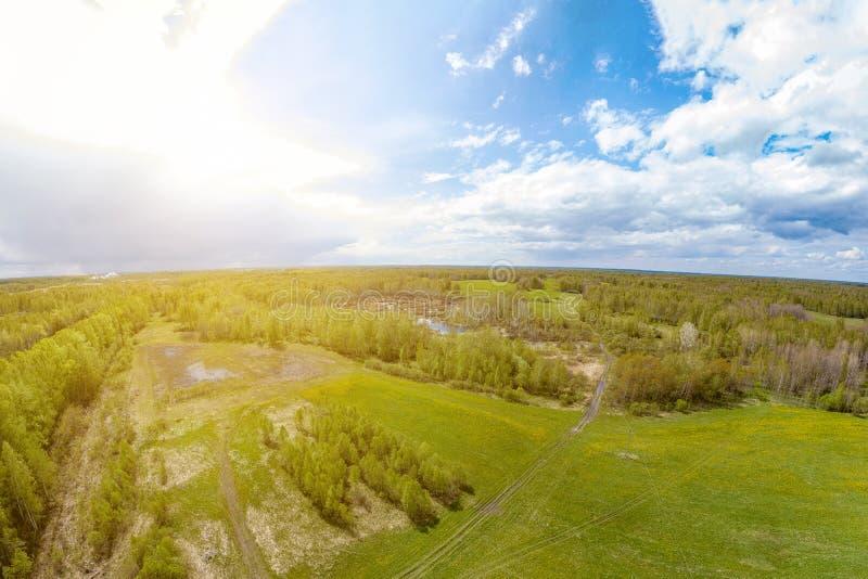 Вид с воздуха панорамы зеленых луга и поля около пути вокруг которого серые и белые облака с голубым небом со страной стоковые изображения