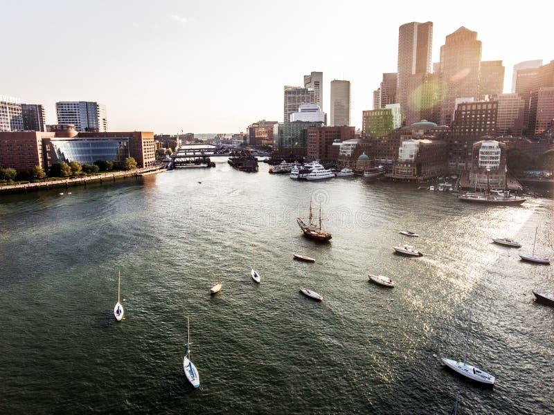Вид с воздуха полета вертолета отображает МАМЫ Бостона горизонта, США во время захода солнца за небоскребами около залива портово стоковые фото