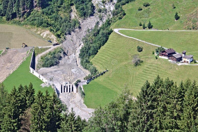 Вид с воздуха потока горы в австрийских Альпах преграженных после массивнейшего селия с деятельностью экскаватора и тележки для т стоковая фотография