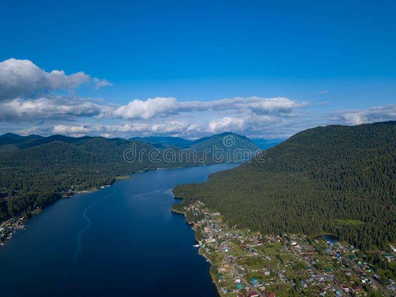 Вид с воздуха рта на широком озере Teletskoye в горах Altai открытым морем, небо с белыми облаками, зелеными деревьями на стоковые фото