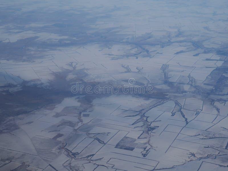 Вид с воздуха снежных гор покрытых облаками Верхняя часть горы покрытая облаками во взгляде зимы от самолета стоковые фотографии rf