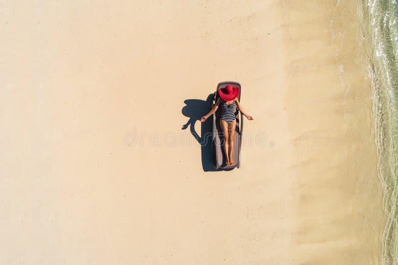 Вид с воздуха тонкой женщины загорая лежать на chairin Сейшельских островах пляжа Seascape лета с девушкой, красивыми волнами, кр стоковая фотография