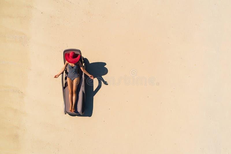 Вид с воздуха тонкой женщины загорая лежать на chairin Сейшельских островах пляжа Seascape лета с девушкой, красивыми волнами, кр стоковые изображения rf