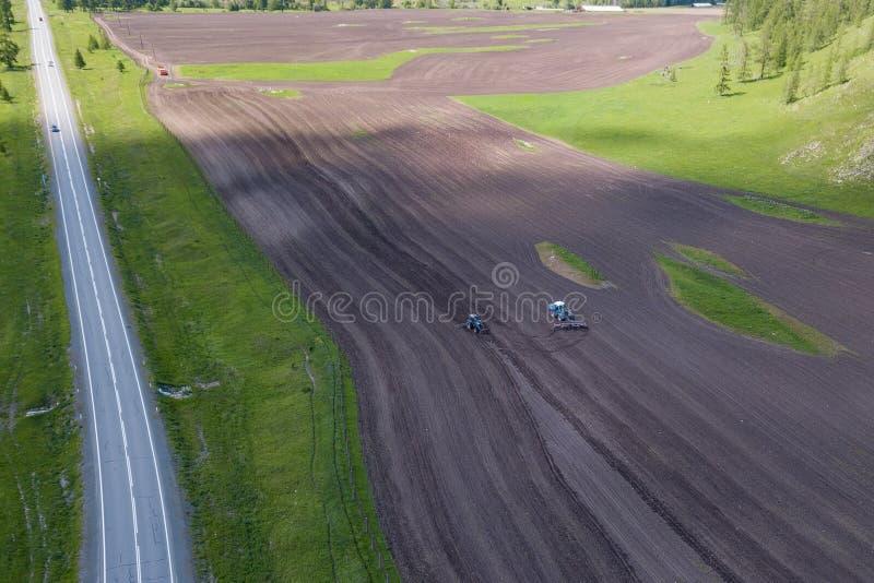 Вид с воздуха трактора фермы в поле во время вспахивать земли для растя еды, овощей и плодов вокруг зеленого дерева с стоковые изображения rf