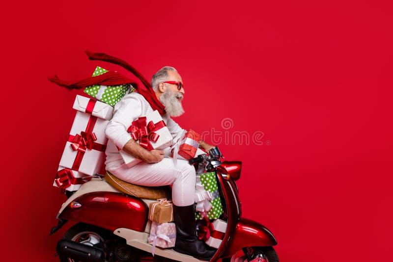 Вид с профиля на красивого фанки-веселого седого седого мужчину, катающегося на моторе, несущего стопку нового желаемого стоковое изображение