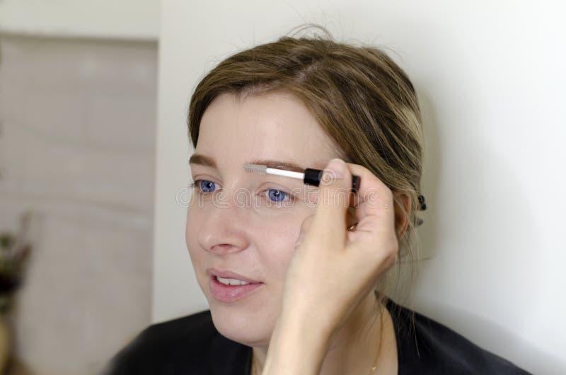 Визажист делает макияж для девушки стоковые изображения