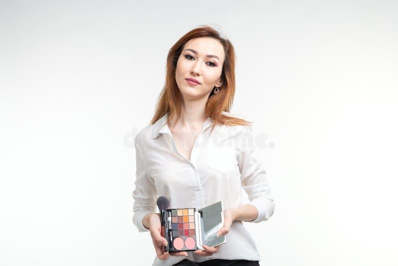 Визажист, красота и концепция косметик - корейский женский художник макияжа с щетками макияжа и палитрой теней глаза стоковые фото