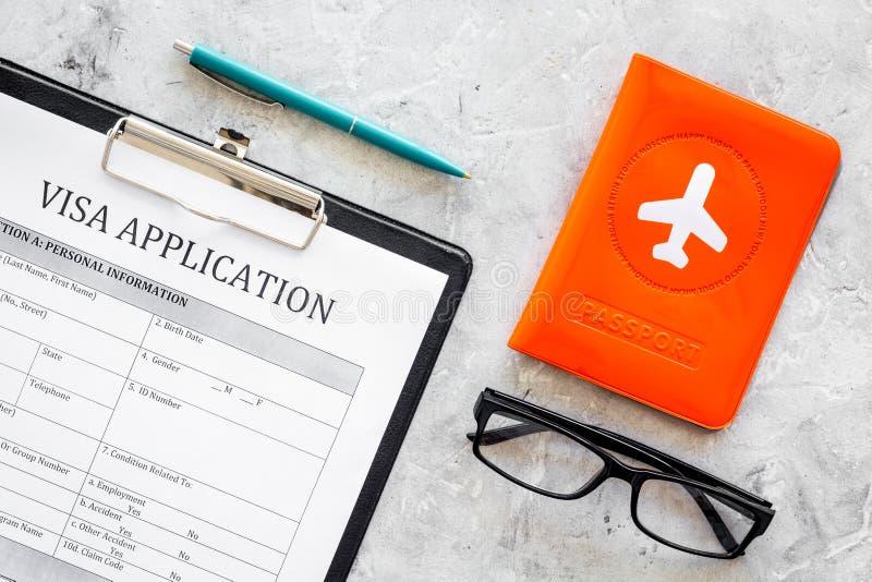 Виза обрабатывая, регистрация Форма заявления на выдачу визы около крышки пасспорта с самолетом на сером взгляд сверху предпосылк стоковая фотография rf