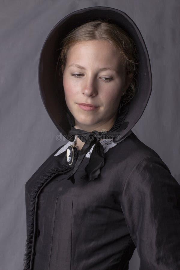 Викторианская женщина в черных лифе и bonnet стоковая фотография