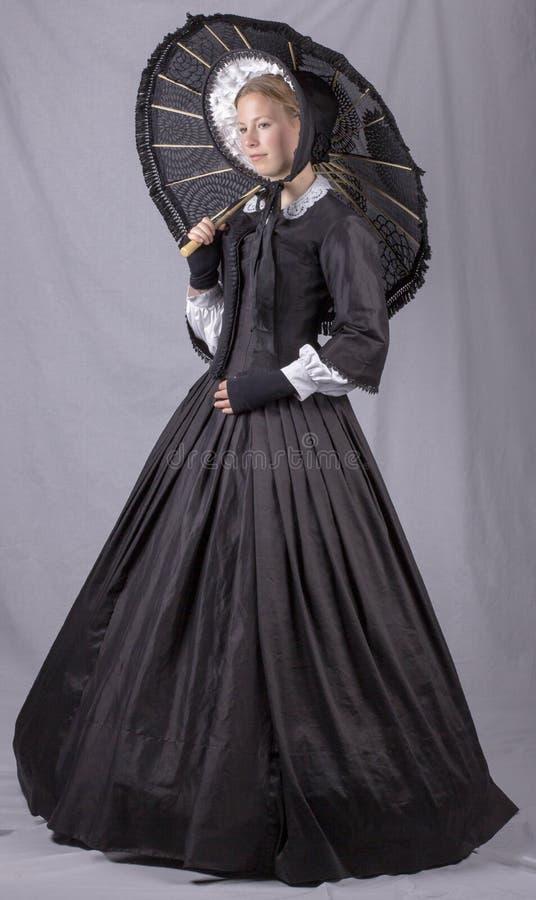 Викторианская женщина в черных лифе, юбке, парасоле и bonnet стоковая фотография