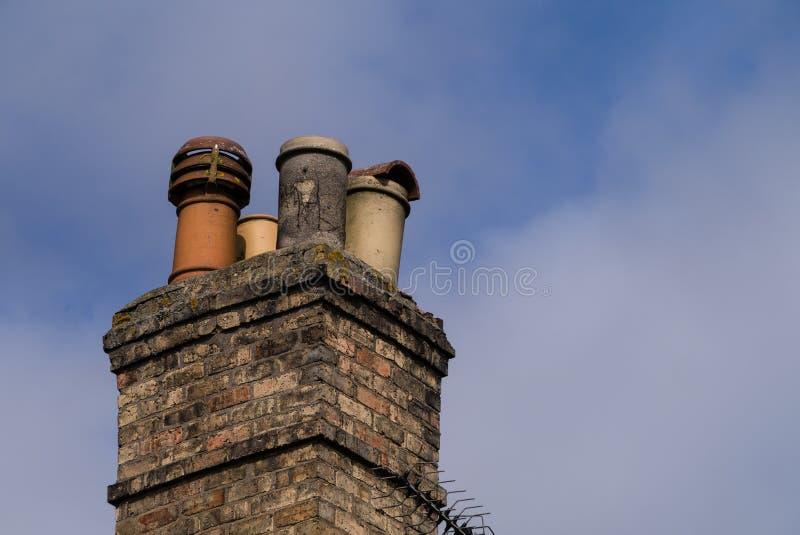 Викторианская отечественная печная труба с 4 сортировала печная труба-баки против ясной предпосылки голубого неба скопируйте косм стоковые изображения