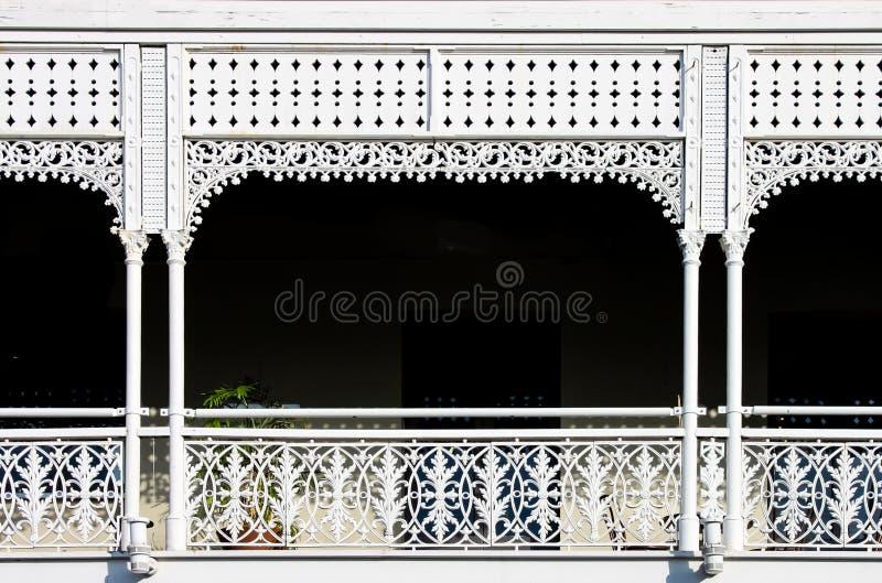 Викторианский декоративный чугунный балкон с заводом на ей но главным образом темнота за белыми покрашенными богато украшенными п стоковое фото