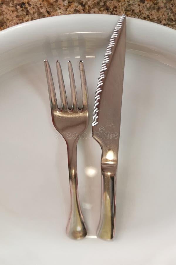 Вилка и нож на пустой плите стоковая фотография
