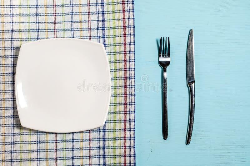 Вилка и нож около пустой плиты на салфетке в клетке на голубой деревянной предпосылке стоковое изображение rf