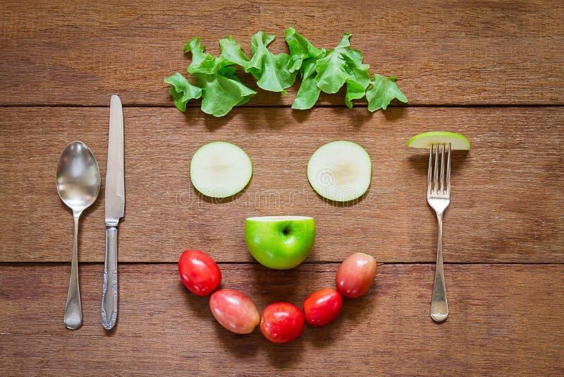 Вилка, ложка, нож и усмехаясь форменные овощи салата на предпосылке grunge деревянной стоковые изображения
