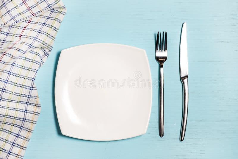 Вилка, нож и пустая плита около салфетки в клетке на голубой деревянной предпосылке стоковое изображение rf