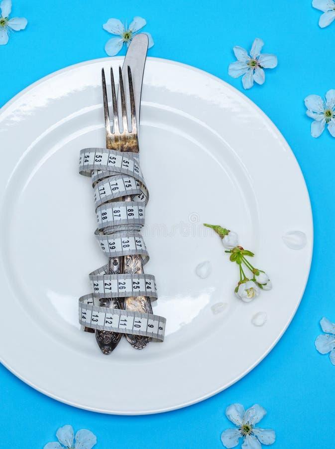 Вилка с ножом в оболочке в измеряя лож ленты на белом rou стоковые фото