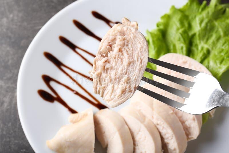 Вилка с частью кипеть филе цыпленка над плитой, крупным планом стоковая фотография