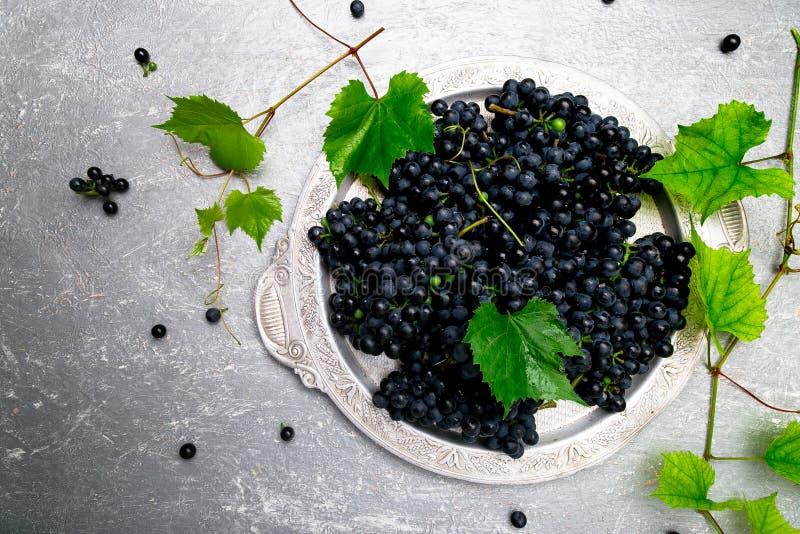Виноградины красного вина в серебряном подносе на серой предпосылке Взгляд сверху скопируйте космос стоковые изображения rf