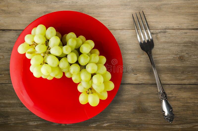 Виноградины на деревянной предпосылке белизна плиты предпосылки изолированная виноградинами стоковое изображение