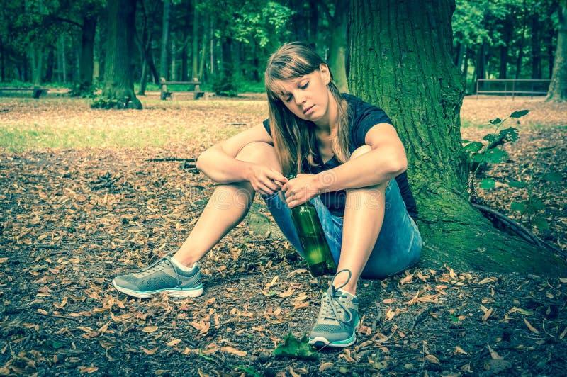Вино женщины выпивая в парке и сидеть под деревом стоковая фотография