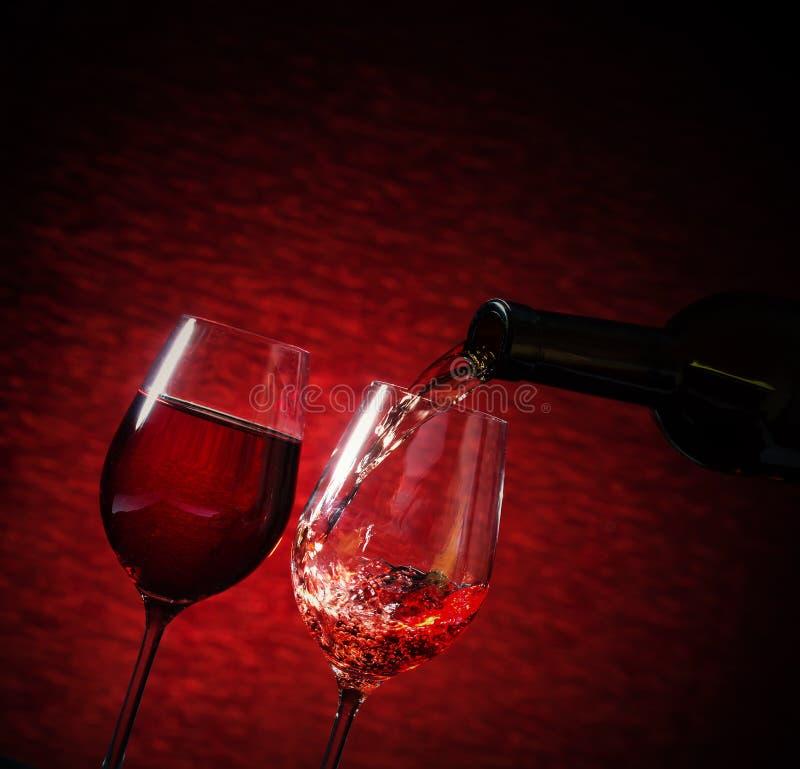 Вино лить в стекло на красной предпосылке стоковое изображение rf