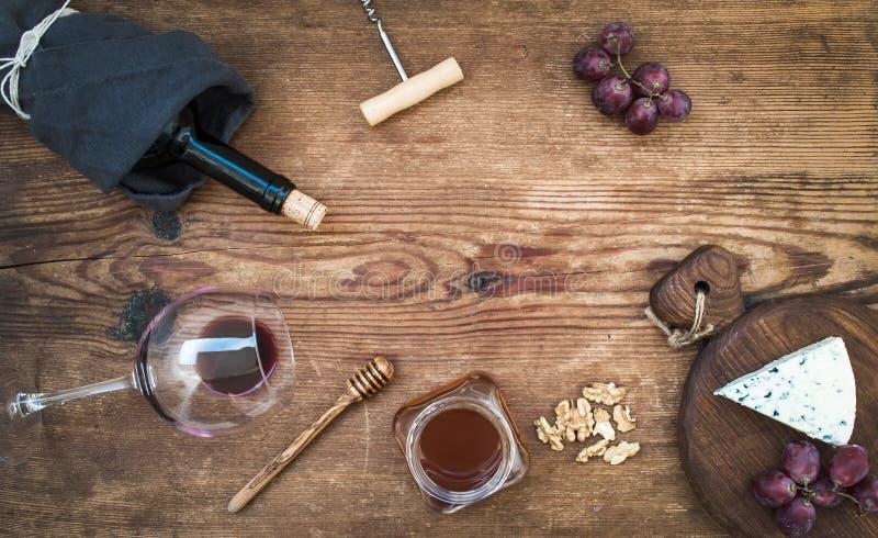 Вино и закуска установили с космосом экземпляра в центре Стекло красного вина, бутылки, corkscrewer, голубого сыра на доске серви стоковые изображения