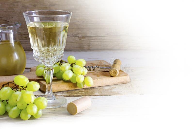 Вино и зеленые виноградины на деревенской древесине, угловой предпосылке на белизне стоковая фотография rf