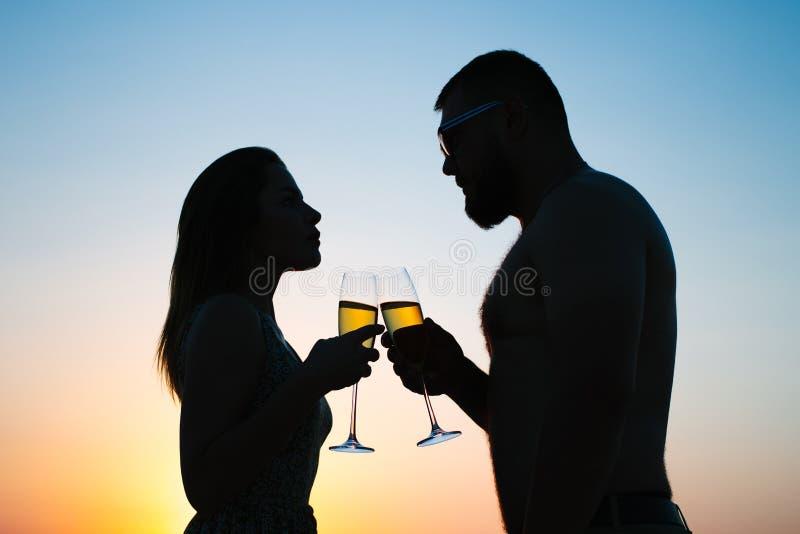 Вино любящих пар выпивая или шампанское во время времени захода солнца, силуэт пары с рюмками на предпосылке захода солнца, челов стоковое фото rf
