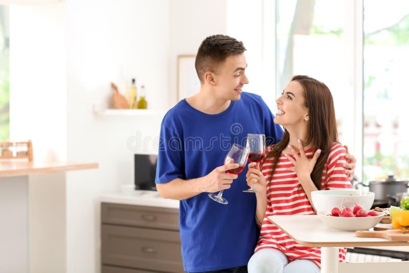 Вино молодых пар выпивая пока варящ совместно в кухне стоковое фото