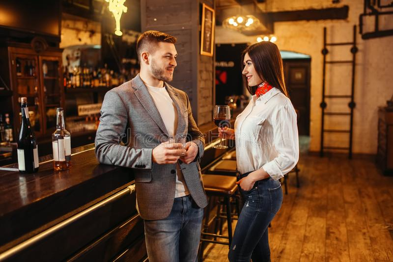 Вино напитков человека и женщины красное на счетчике бара стоковое изображение rf