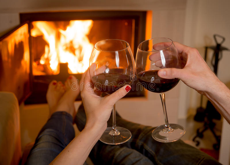Вино пар выпивая перед огнем стоковая фотография