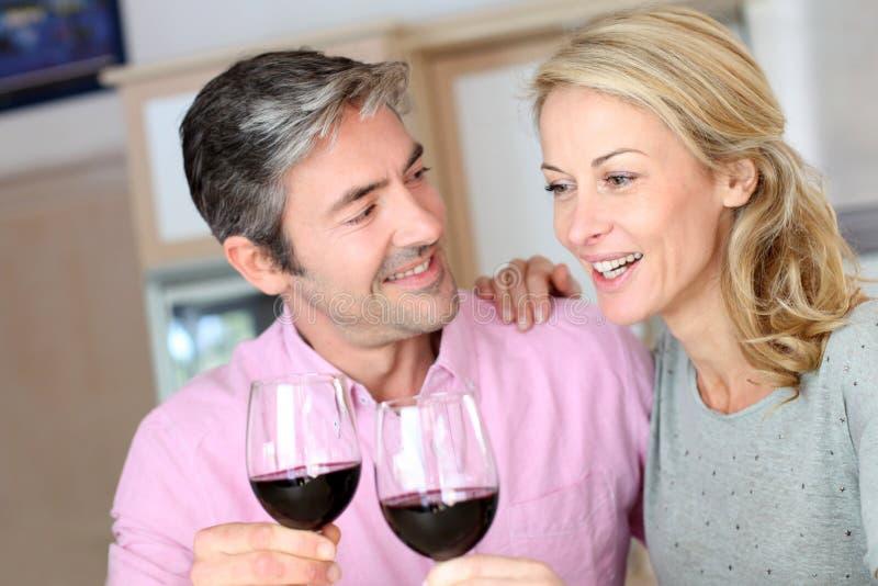 Вино радостных пар выпивая дома стоковые фотографии rf