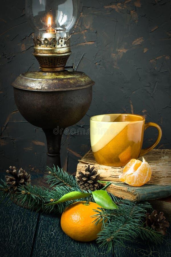 Винтажная атмосфера рождества: лампа керосина, книги, tangerine стоковое изображение rf
