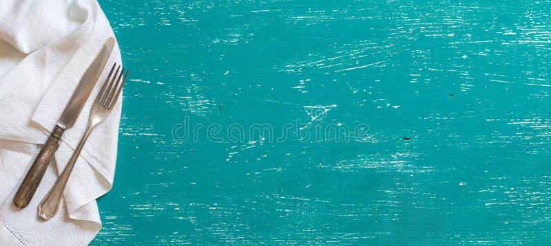 Винтажная вилка и нож на салфетке на древесине бирюзы стоковое фото