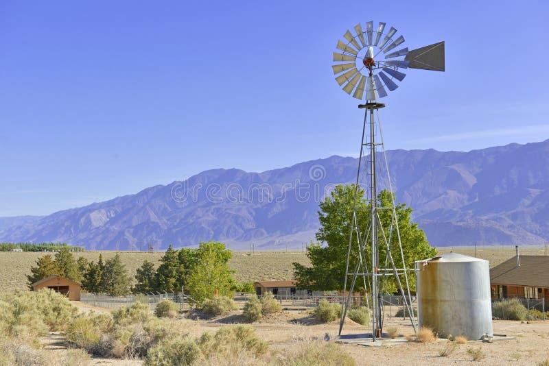 Винтажная водяная помпа/ветрянка в сельском ландшафте стоковое фото rf